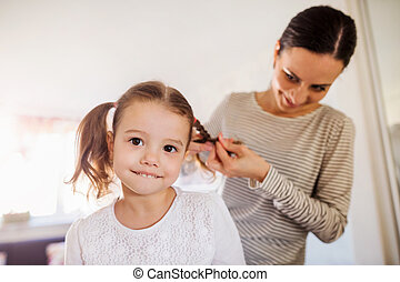 Mother braiding hair of her daughter in the morning