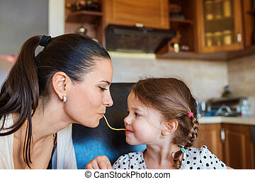Mother and daughter in the kitchen, eating spaghetti together