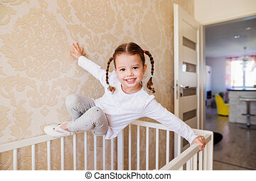 Little girl with braids hanging above white baby crib - Cute...