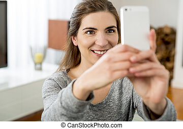 A selfie at home - Beautiful woman taking a photo of herself...