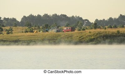 Fog rambles over a lake in summer with camp on background -...
