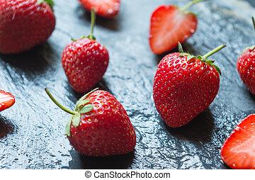 Strawberry fruit on black stone background