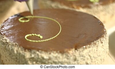 Chocolate cake with cream decoration Tool applying cream on...