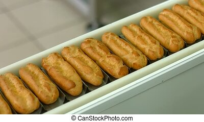 Eclairs quickly moving on conveyor. Row of eclairs on...