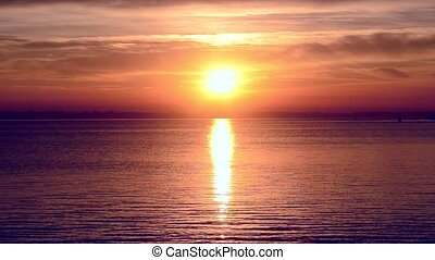 Beautiful sunrise or sunset above sea with light reflected in water
