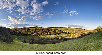 Beautiful large panorama landscape of countryside on bright Spring morning with blue sky