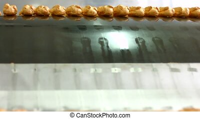 Eclairs slide down conveyor line Rows of eclairs on conveyor...