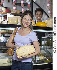 Happy Woman Holding Cheese In Front Of Grocery Store