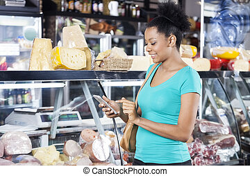 Woman Using Cell Phone In Grocery Shop - Smiling young woman...