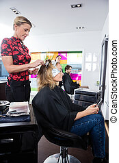 Woman Getting Hair Colored In Beauty Salon - Mature woman...