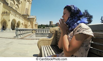 Girl sits on bench and prays - Beside Holy Trinity Cathedral...
