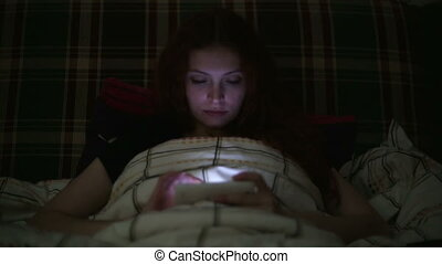 Young woman using smartphone lying on bed at home at night