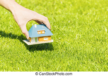 new home concept, hand putting house scale model on grass