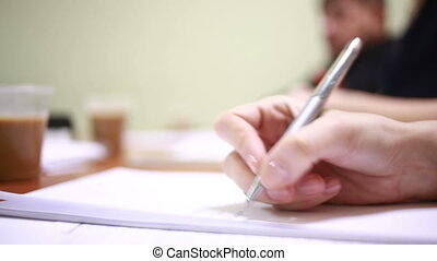 Businesswomans hand with pen completing personal information...