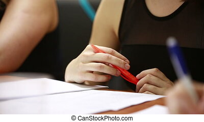 Businesswoman's hand with pen completing personal...