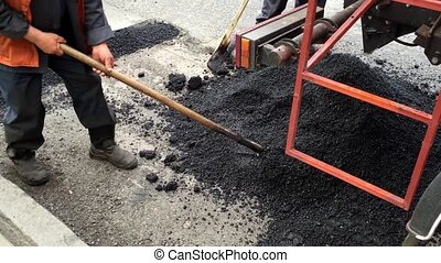 Workers with shovels repairing asphalt. Men repair damaged...