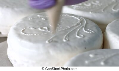 Tool applying cream on cakes. White cakes with ornament....