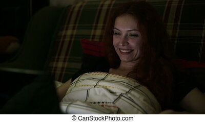 Young woman with a laptop talking on Skype while lying in...