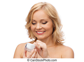 happy woman with cream jar - beauty, people, skincare and...