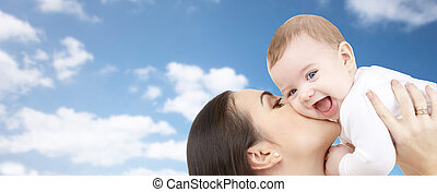 happy mother kissing her baby over blue sky - family,...