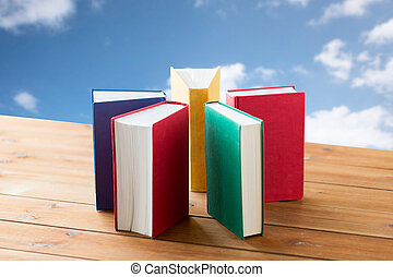 close up of books on wooden table - education, school,...