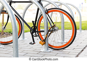 close up of bicycle locked at street parking - transport,...