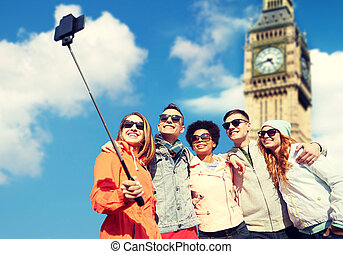 smiling friends taking selfie with smartphone - tourism,...
