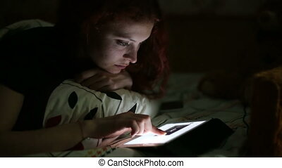 Young woman with the tablet received a text message while lying on a bed at home at night