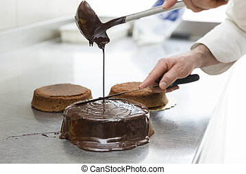 confectioner - pastry chef covering cake with melted...