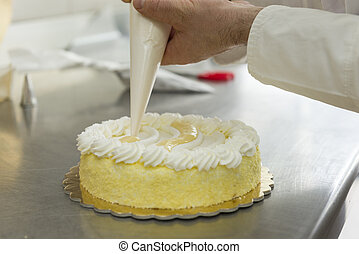 confectioner - pastry chef garnish a cake with cream