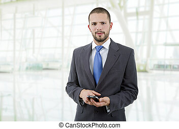 on the phone - young business man looking to his phone, at...