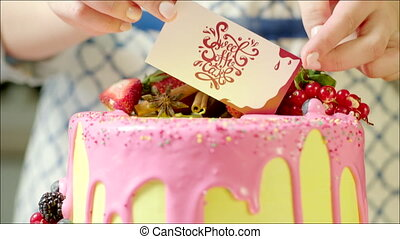 Delicious cake with home bakery card - Shot of female hand...