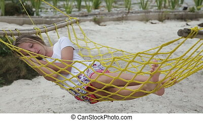 Young girl relaxing in a hammock on the sea beach - Child...