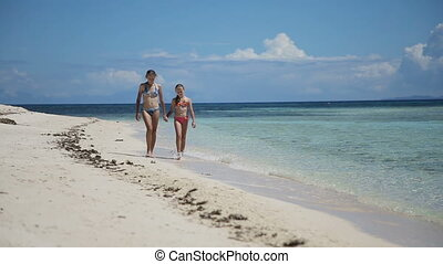 Two girls walking on a tropical beach