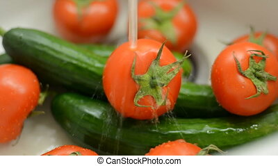 Wash vegetables in a sink Fresh tomatoes and cucumbers under...