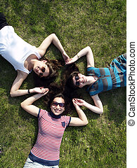Girls laying on grass - Three young girls laying on grass...