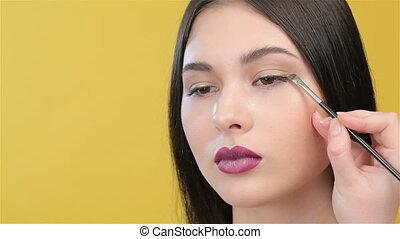 Close up of visagist applies an eyeliner
