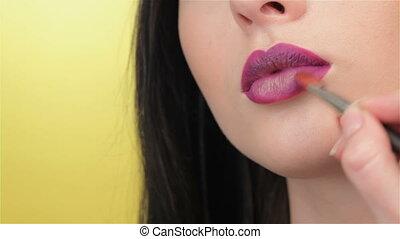 Girl blinks while visagist painting her lips