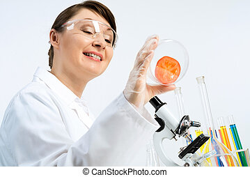 GMO check - Attractive female scientist making tests of...