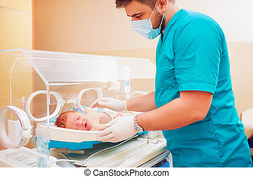 medical staff taking care of newborn baby in infant...