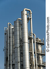 Distillation columns at industrial plant or refinery against...
