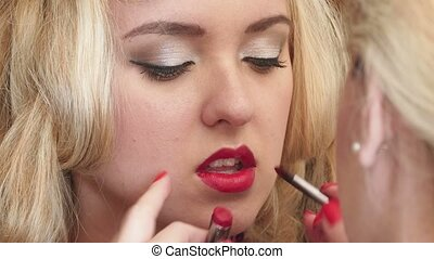 Make-up for photo session - Makeup artist apply the lipstick...