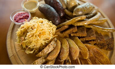 Plate with beer snacks- potato, sausages, cabbage and bread