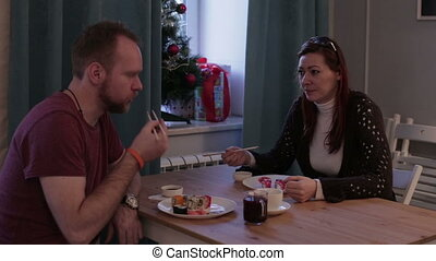Friends eats sushi at the table - Caucasian man and woman...