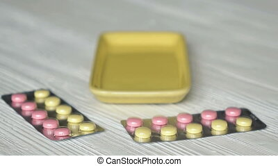 Hand folds pills in container placed on the table