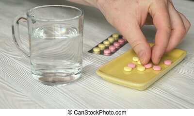 Man's hand takes the pills from a yellow container