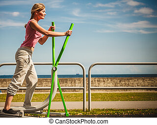 Active woman exercising on elliptical trainer - Active young...