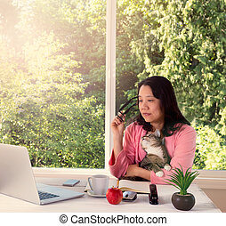 morning light hitting woman and her cat while at home working