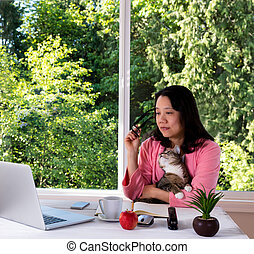 Mature woman holding her pet cat while working from home in morning attire