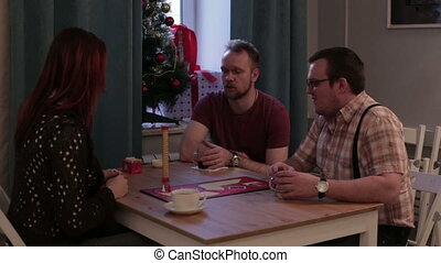 Young people play a board game in a cafe - Caucasian people...